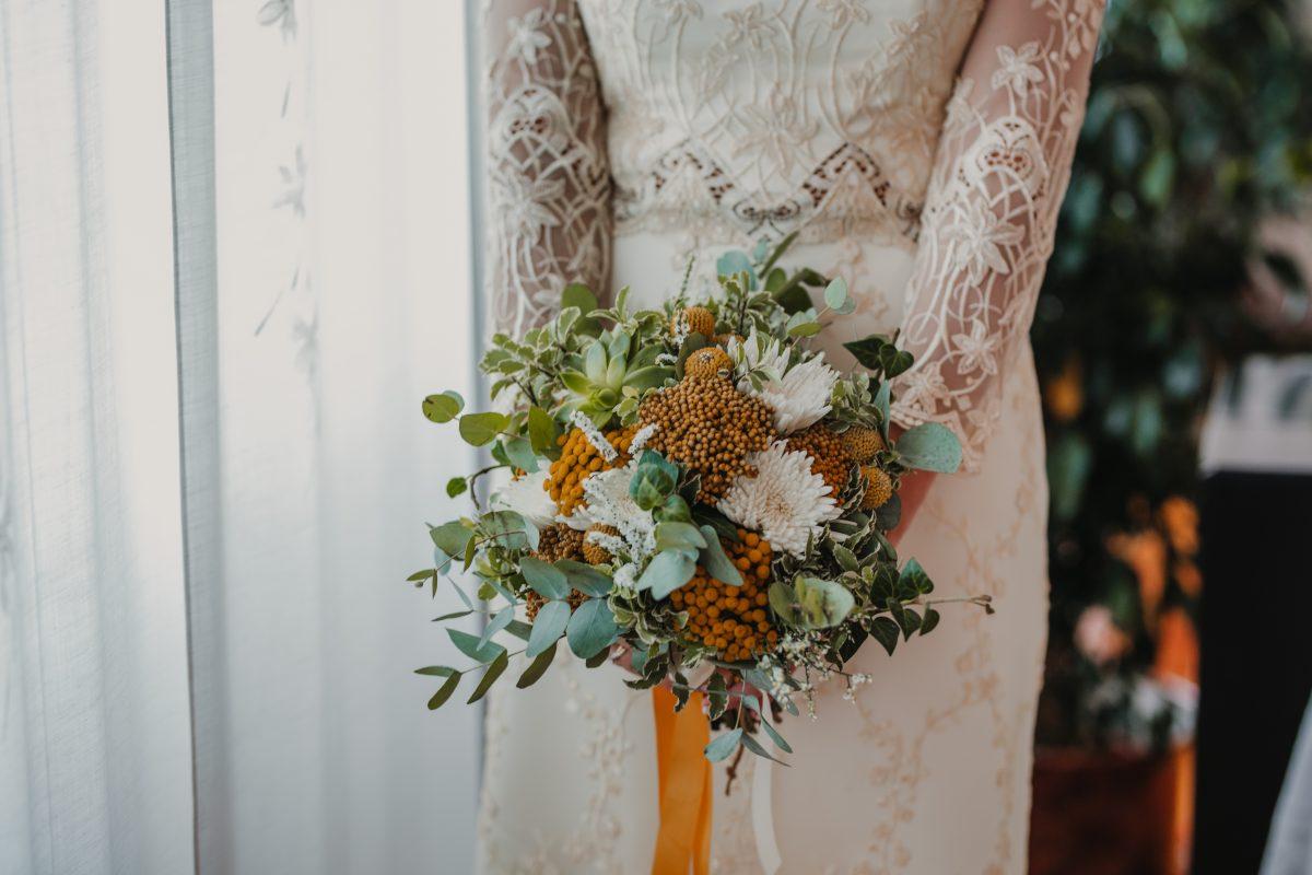 In questa foto il bouquet da sposa con piante e fiori gialli e bianchi