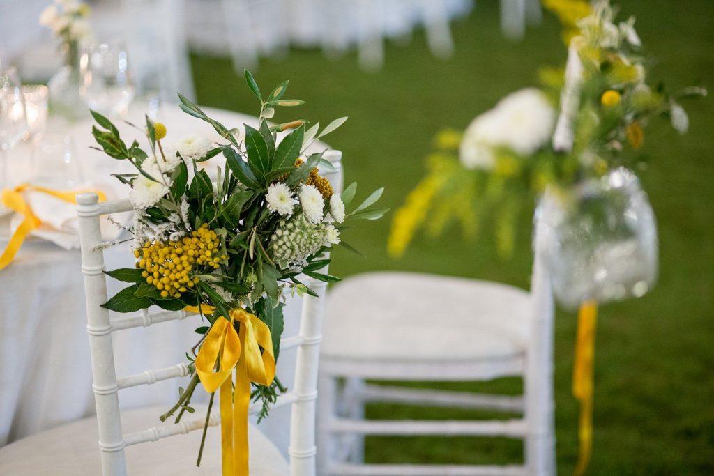 In questa foto un allestimento floreale su sedie Tiffany in bianco e giallo