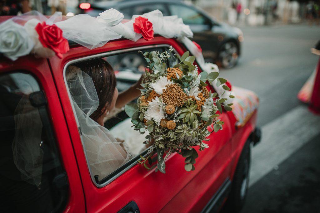 In questa foto la sposa a bordo della sua auto con il bouquet nei toni del giallo