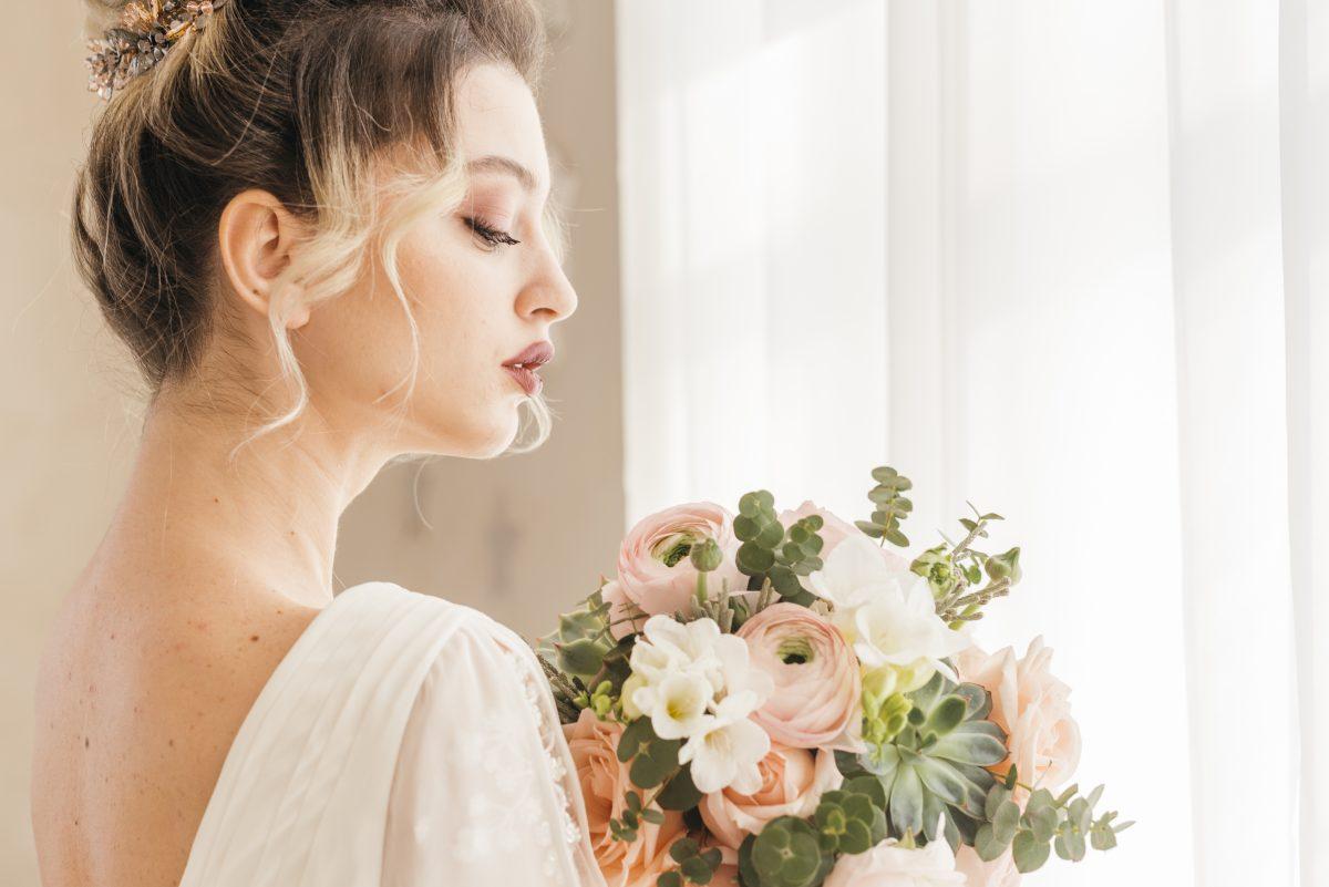In questa foto una sposa in posa con il bouquet per il suo shooting di matrimonio