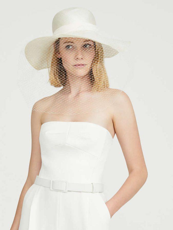 In questa foto una modella indossa un cappello a falda larga, modello Borsalino, al posto del classico velo da sposa