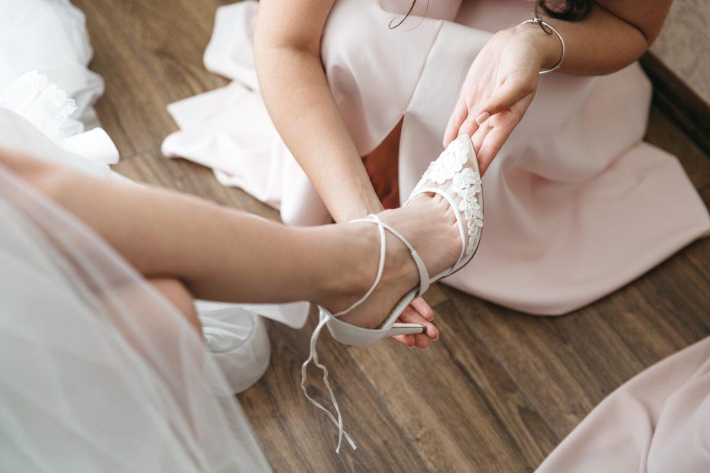 In questa foto una sposa indossa le sue scarpe da sposa con richiami floreali