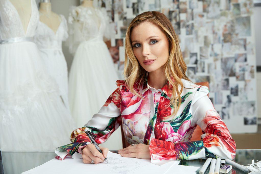 In questa foto la designer britannica e co-fondatrice di Marchesa, Georgina Chapman, seduta alla sua scrivania