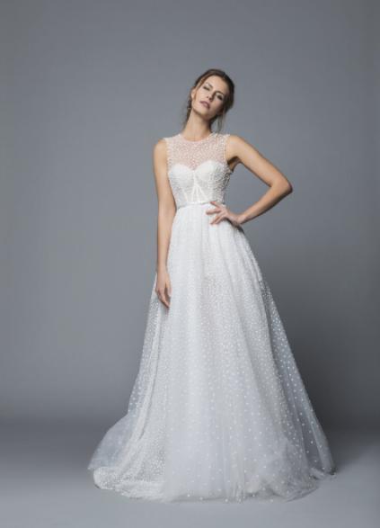 In questa foto una modella indossa un abito da sposa in plumetis di Antonio Riva