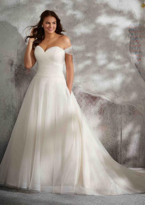 In questa foto una modella indossa un abito da sposa curvy