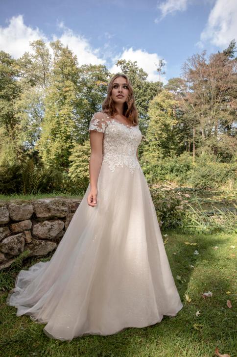 In questa foto una modella indossa un abito da sposa curvy di Le Papillon by Modeca