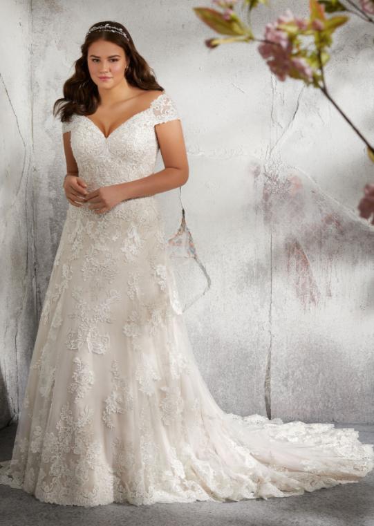 In questa foto una modella indossa un abito da sposa curvy con mezze maniche