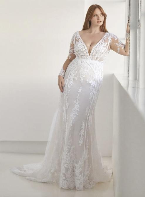 In questa foto una modella indossa un abito da sposa curvy firmato Pronovias