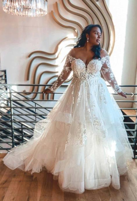 In questa foto una modella indossa un abito da sposa curvy di Essence of Australia