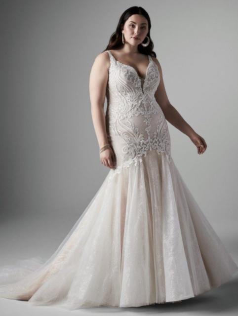 In questa foto una modella indossa un abito da sposa curvy firmato Sottero and Midgley