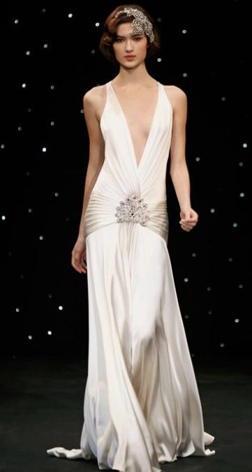 In questa foto una modella indossa un abito da sposa anni 20, con profondissima scollatura a V, di Jenny Packham