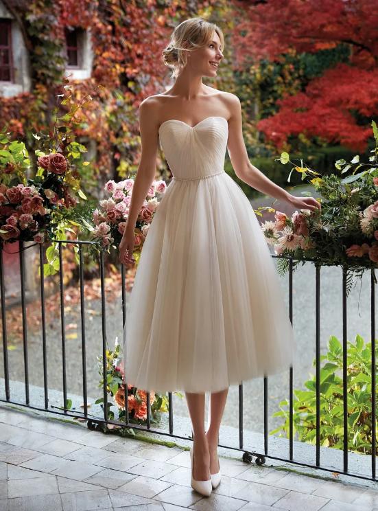 In questa foto una modella indossa un abito da sposa anni 50 con scollatura a cuore e vaporosa gonna a ruota lunga fino a metà gamba di Nicole