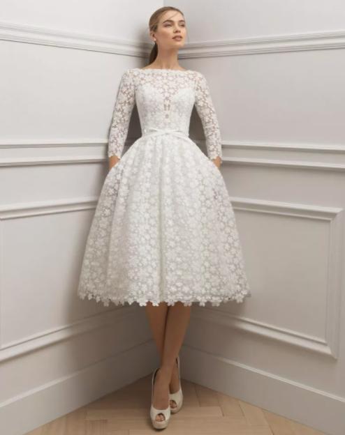 In questa foto una modella indossa un abito da sposa anni 60 in pizzo, con gonna a palloncino lunga fin sotto il ginocchio, di Rosa Clarà