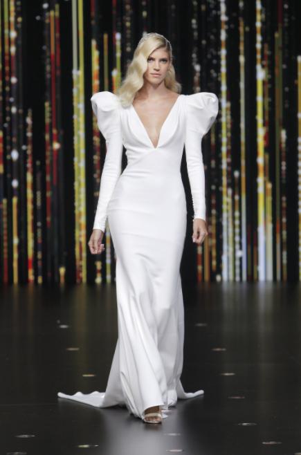 In questa foto una modella indossa un abito da sposa in stile anni 80 di Pronovias: l'attenzione è tutta sulle spalline maxi e a punta