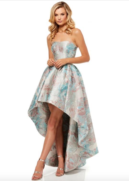 In questa foto una modella indossa un abito da cerimonia più corto davanti e lungo dietro.