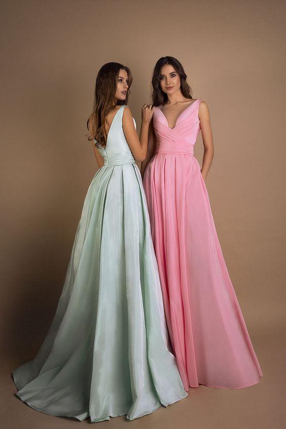 In questa foto due modelle indossano vestiti per damigelle del matrimonio nei colori del rosa e del turchese