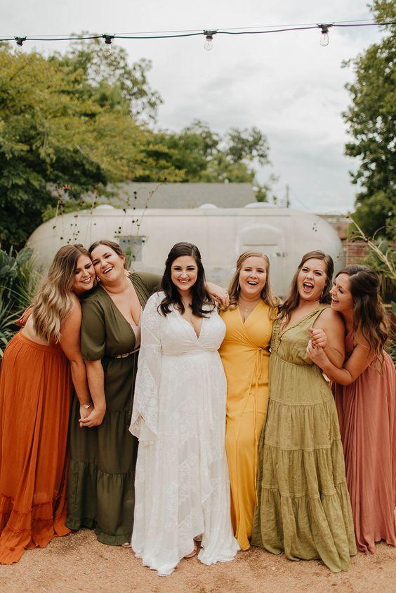 In questa foto una sposa con le damigelle: le ragazze indossano abiti di modelli e colori diversi, nei toni autunnali del verde, ocra, porpora