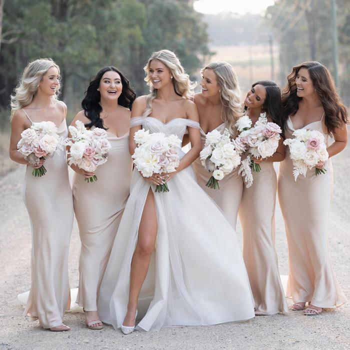 In questa foto una sposa insieme alle sue 5 damigelle vestite color avorio