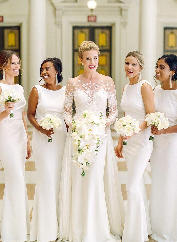 In questa foto una sposa e le sue damigelle vestite tutte di bianco