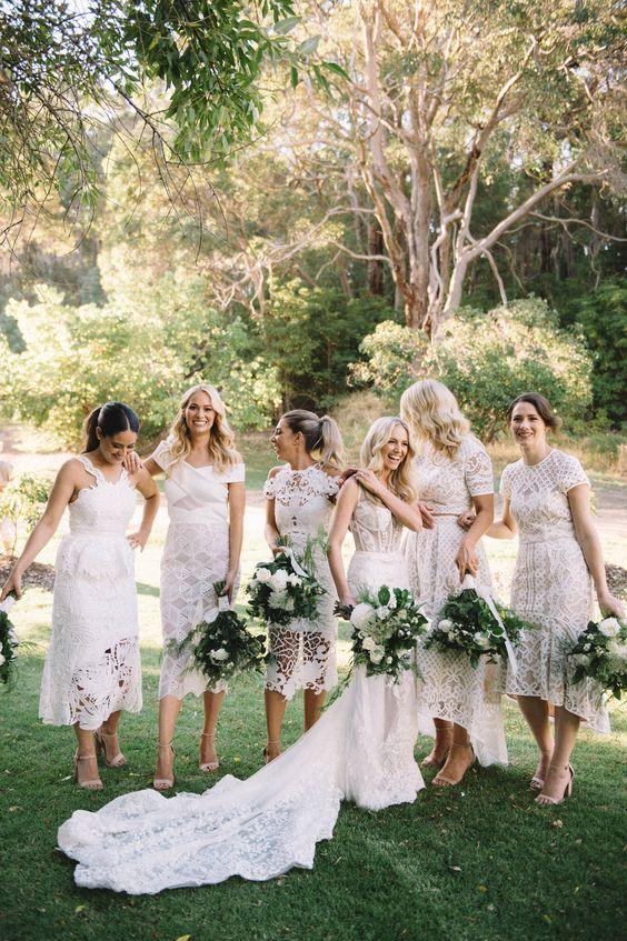 In questa foto una sposa vestita di bianco insieme alle sue damigelle di matrimonio anche loro con vestiti bianchi ma longuette