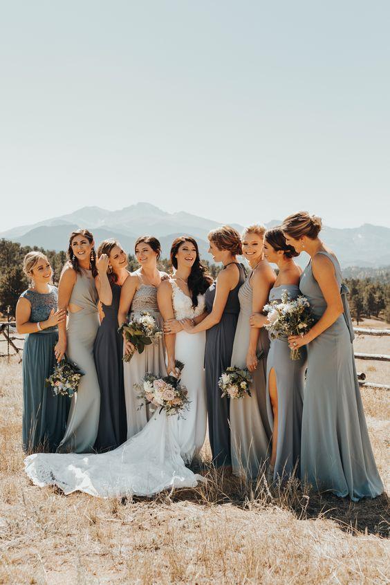 In questa foto una sposa con le sue damigelle, vestite nei toni dal celeste al blu, mentre posano per una foto in un campo