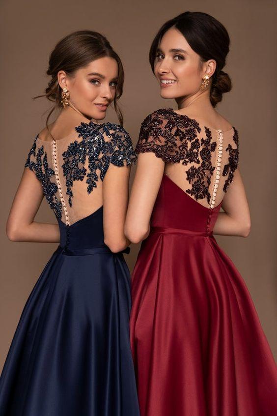 In questa foto due modelle indossano abiti perfetti per le damigelle del matrimonio: stesso modello, con ricamo su spalle e schiena, colori diversi in blu e bordeaux