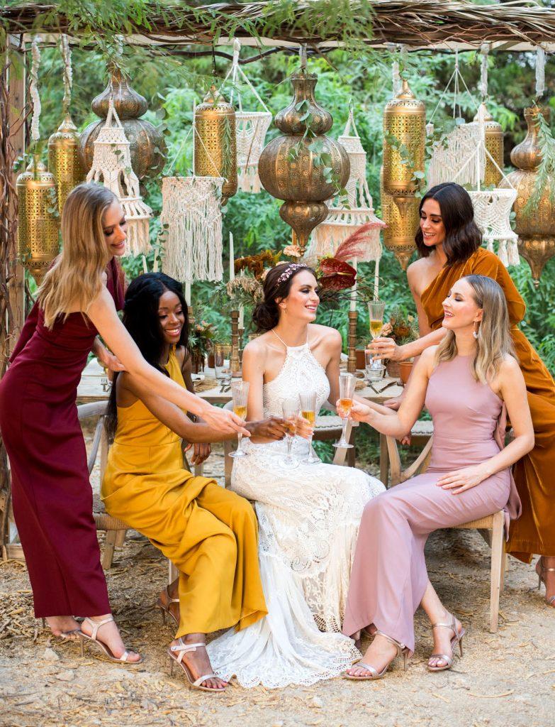 In questa foto le damigelle con la sposa indossano abiti perfetti per un matrimonio in stile Boho Chic: i colori sono ocra, arancione scuro, rosa antico e bordeaux
