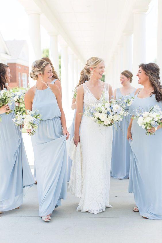 In questa foto una sposa circondata dalle damigelle che indossano abiti celesti