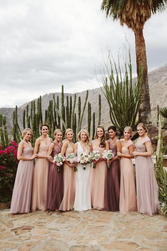 In questa foto una sposa con le sue 8 damigelle di nozze vestite nei toni del pesca, lavanda e ametista