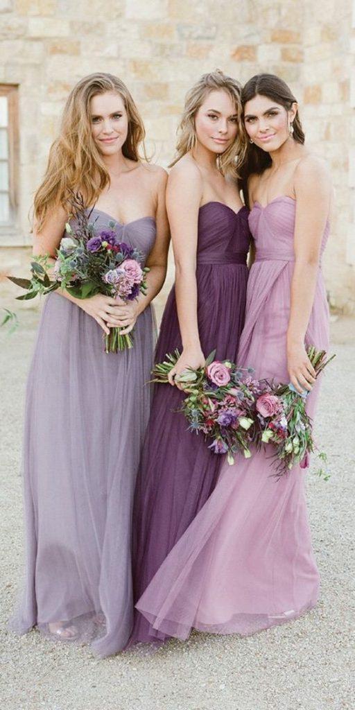 In questa foto tre damigelle di matrimonio vestite con abiti uguali, ma di sfumature del viola differenti