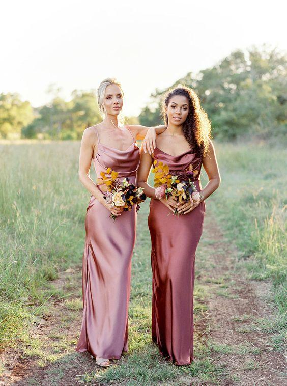 In questa foto due damigelle della sposa con abiti sottoveste in raso di seta nei toni del marsala chiaro e scuro
