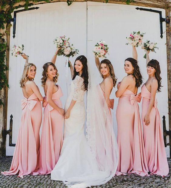 In questa foto una sposa insieme alle sue damigelle vestite di rosa: il modello dell'abito è uguale per tutte, a sirena e con fiocco sul retro