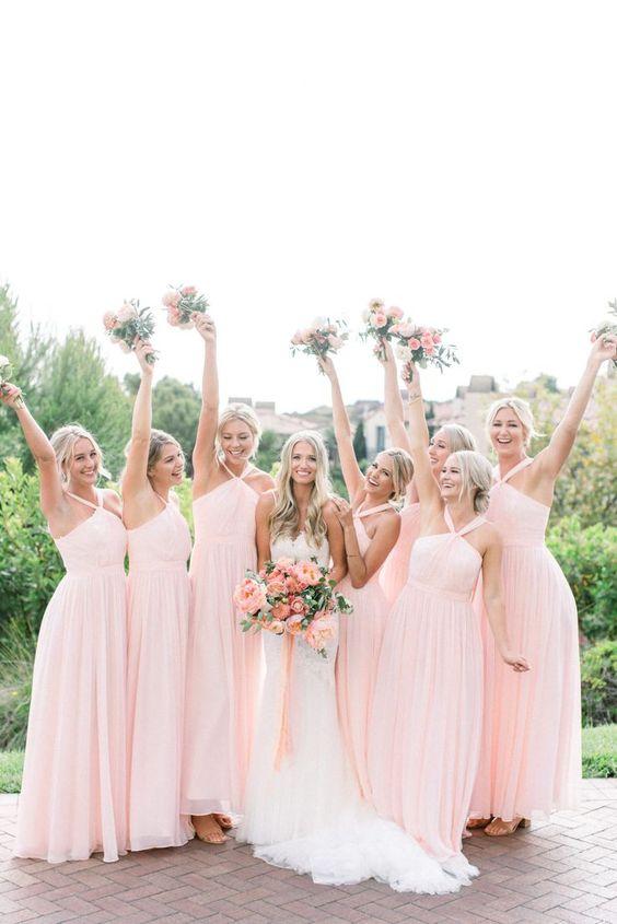 In questa foto una sposa e le sue damigelle vestite con abiti rosa confetto, tutti dello stesso modello. Tra le mani hanno bouquet con fiori della stessa tonalità di rosa
