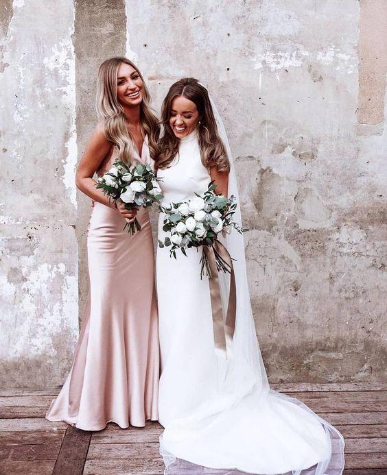 In questa foto una sposa con la sua damigella d'onore vestita con un abito sottoveste in seta rosa, sorridenti e con in mano i loro bouquet floreali