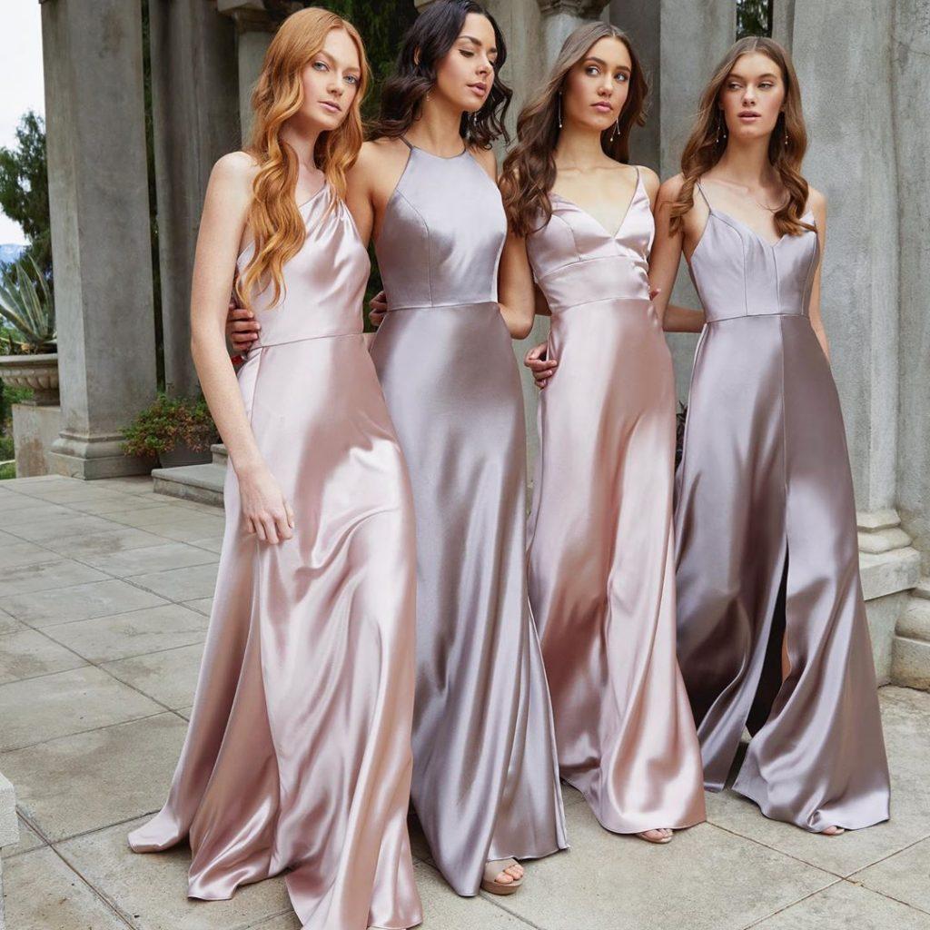 In questa foto quattro modelle indossano abiti per damigelle di nozze nei toni del rosa e del lavanda