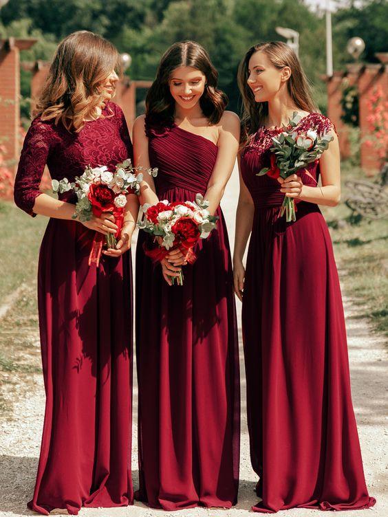 In questa foto tre damigelle indossano abiti lunghi colore bordeaux con bouquet di fiori in coordinato