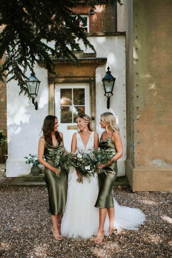 In questa foto una sposa con le sue damigelle vestite con abiti sottoveste, in raso di seta colore verde