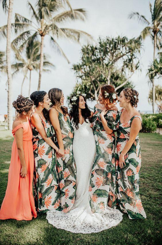 In questa foto una sposa con le sue damigelle vestite con abiti a fantasia tropicale. La damigella d'onore ha un abito diverso dalle altre, color pesco