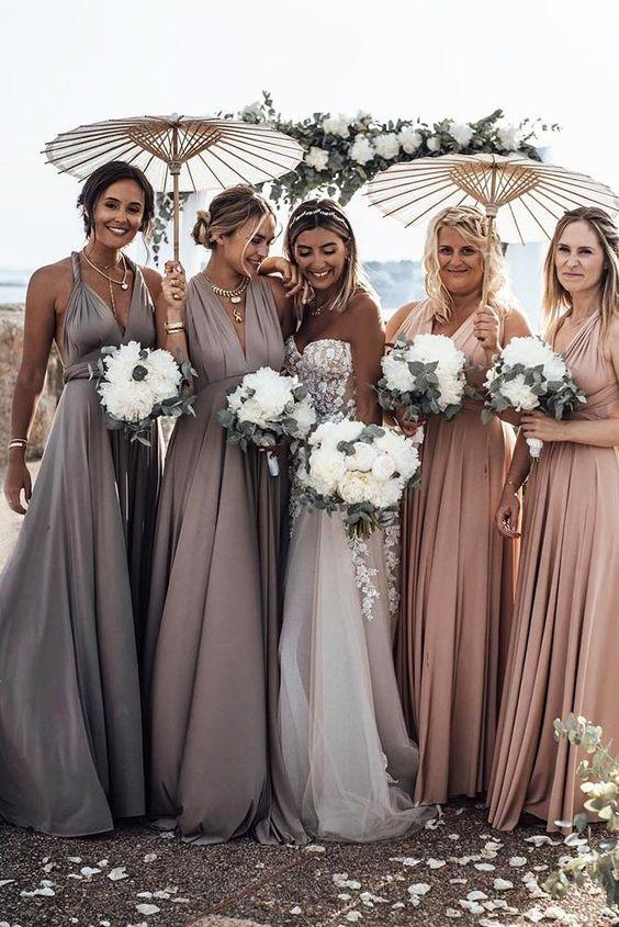 In quesa foto una sposa con le sue damigelle vestite nei toni che sfumano dal rosa al lavanda. Tengono tra le mani i bouquet e gli ombrellini di carta per ripararsi dal sole