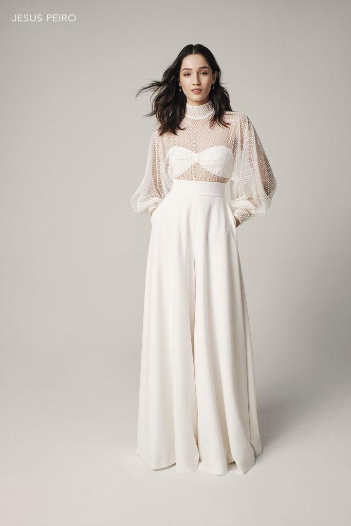 In questa foto una modella indossa un abito da sposa con pantaloni a vita alta e blusa trasparente di Jesus Peiro
