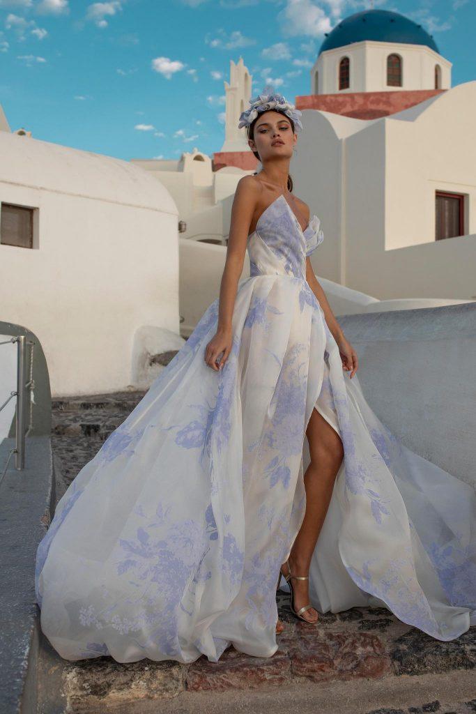 In questa foto una modella indossa un abito da sposa colorato e con spacco di Ricca Sposa, perfetto per un matrimonio sull'isola