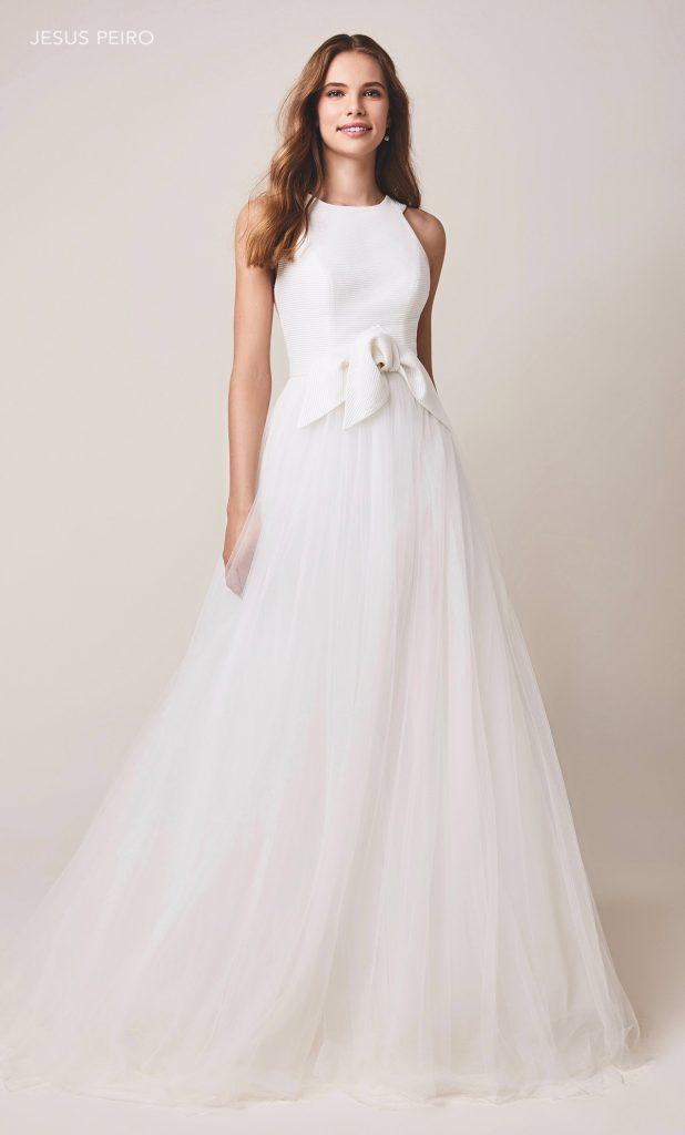 In questa foto una modella indossa un abito da sposa con gonna in organza di Jesus Peiro