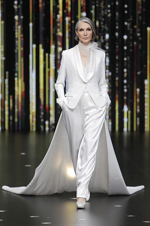 In questa foto una modella over indossa un abito da sposa taglio smoking pensato per donne mature