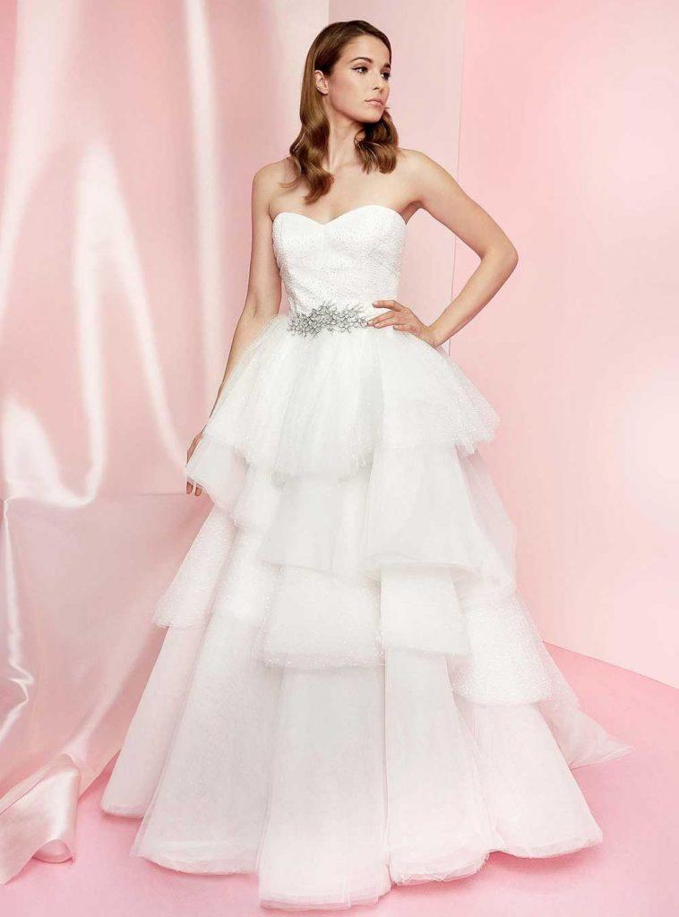 In questa foto una modella indossa un abito da sposa a balze in tulle della collezione Carlo Pignatelli