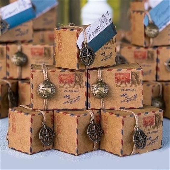 In questa foto delle bomboniere per nozze a tema viaggio a forma di pacchi postali chiuse da mappamondi e bussole in ottone
