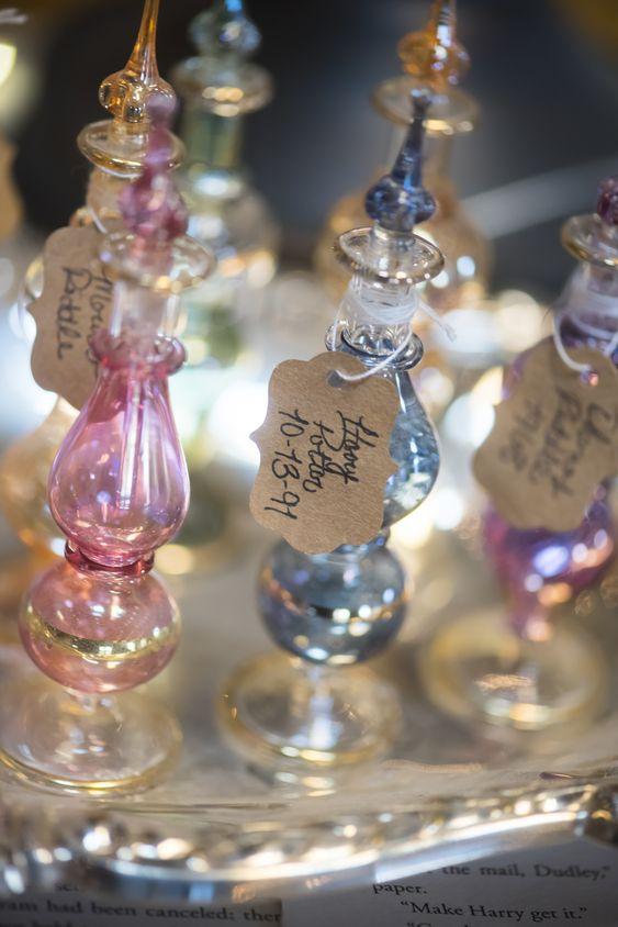 In questa foto bottigliette di vetro rosa e azzurre con targhette in cartoncino, perfette come bomboniere matrimonio a tema Harry Potter