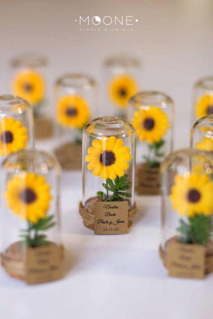 In questa foto piccole bomboniere per un matrimonio a tema girasoli. I fiorellini sono racchiusi in una piccola campana di vetro