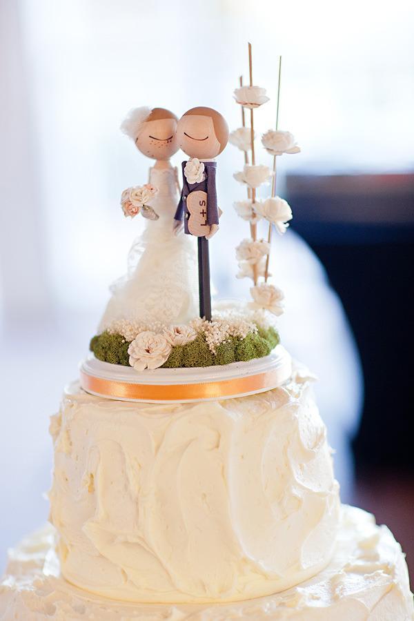 In questa foto un cake topper personalizzato con due sposi che si tengono per mano
