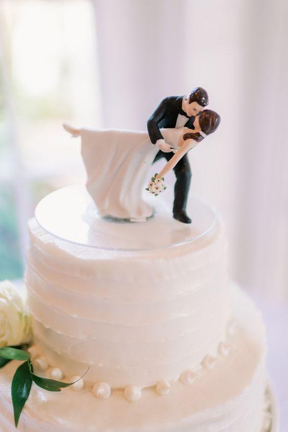 In questa foto le statuine di due sposi mentre ballano, da utilizzare come cake topper