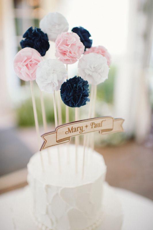 In questa foto una cake topper semplicissimo, realizzato con una targa in legno con su incisi i nomi degli sposi e alcuni pompom di carta colorata